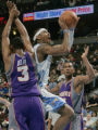 Denver Nuggets forward Carmelo Anthony, splits Phoenix Suns defenders Boris Diaw, left, and...
