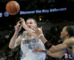 Denver Nuggets rookie forward Linas Kleiza, left, passes the ball in the fourth quarter of play...