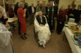 Stan Gray, 76 (cq)  son to Harold Gray, 105 (cq) wheels his father through a gathering of friends...