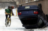 (DENVER, Colo., Feb. 03, 2005) Cyclist ride their bicycles by a vehicle that slid off the road...