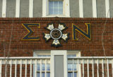 The Greek letters Sigma and Nu flank the organization's badge on the front of fraternity house on...
