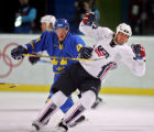 Team U.S.A.'s Mike Modano (#9) gets tied up Team Sweden's Samuel Pahlsson (#26) during the first...