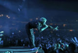 Coldplay lead singer Chris Martin reaches out at the crowd as he performs with his group Coldplay...