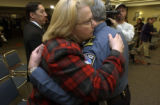 Councilwoman Margaret Radford, left, in red plaid, white hair, glasses, (cq), hugs Chief Luis...