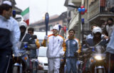 An Olympic Torchbearer makes his way through the main street of Settimo Torinese Wednesday as most...