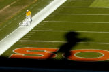 A worker paints the out of bounds line while the shadow of the Denver Bronco falls on the field...