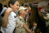 SFC Gary Villalobos, cq, 2/3 ACR, kisses his wife Sandra, cq, while hugging his son Anthony, 8,...