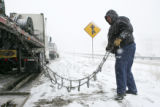 Trucker Ted Hines (cq), of Albuquerque, NM, prepares to put chains on his trcuk on I-70 by the...