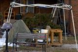 **1/25/06** A bench, wooden glider, and planter stand underneath a canopy frame in front of...