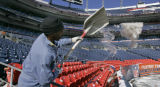 Richard Jennings shovels out the heavy wet and slushy snow from the stadium.  At Invesco Field, in...