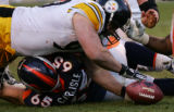 1816 Steelers #90 Travis Kirschke reaches for the ball as he flies over Broncos #65 Cooper...