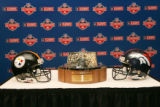 Lamar Hunt Trophy with a Steeler helmet and a Broncos helmet at the Broncos press conference for...