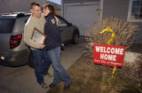 SSGT Philip Mitchell hugs his wife Carrie Mitchell in the front of their home after his...