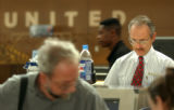 [Denver, CO - Shot on: 6/28/04]  United Airlines ticket agent Rob McCloskey helps passengers with...