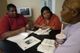 Sean and Delonda Adams, left and center, talk with Wendy Wilkins, right, of Aurora about her...