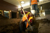 Omar Valdez (cq), a worker for Pipeline Industries, fills in a hole in the entry way of Littleton...