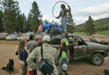 Earnest Ray Berbert (cq), 46, top,  helps fellow Rainbow Family members load up his jeep to...