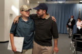 Keegan Price, cq, 12, helps his father Lance Price, cq, as he leaves a press conference during...