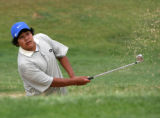 Dominique Johnson (cq), 15, hits out of a sand trap during a practice a round of golf at Murphy...