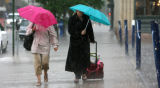 Two unidentified pedestrians brave the heavy afternoon rain through downtown Denver Monday July 3,...