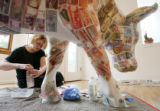 Artist Cheryl Cusick glues currency from all over the world on one of the 150 cows that will be...