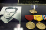 A photo of gunner's mate first class Robert Wills hangs in a display case with his medals,...