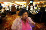 Helen Mitchell, of Aurora, smokes while playing a machine on the gaming floor of a casino in...