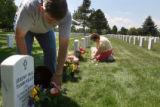 Sam and Mary Holder, cq, Littleton, put flowers at her son SSG Sam Holder's grave as well as other...