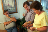 Sam Holder, cq, left, Jo Burns, cq, and Mary Holder, cq, look at photos of Marines who served with...