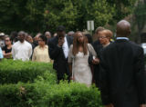 Felecia Blackmon-Ford, white dress, the mother of Michael J. Ford, heads into the Pipkin Chapel...