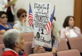 Karen Trujillo (cq) from Denver holds up a sign before HB06S-101 Eligibility for Economic...