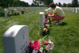 Mary Holder, cq, Littleton, puts flowers at her son SSG Sam Holder's grave on Sunday, July 16,...