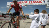 Adam Nash, 5, of Denver hands out a medal to a passing unidentified cyclist, Monday  July 24, 2006...
