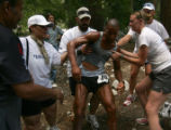 Crewmembers help David Goggins, center, of Chula Vista, center, to his feet after he finished...
