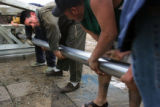 Salvador Tovar, cq, left, works on a piece of machinery for an oil drilling truck he and his...
