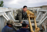 Salvador Tovar, cq, center, works on a piece of machinery for an oil drilling truck he and his...