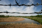 MJM905 Barbwire fence surrounds the South Platte River Thursday.  Officials are worried about...