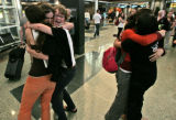 Anna, far left, Gali, middle, and Lily all embrace at the arrivals area of the terminal building...