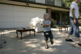 Across the street from the Campbell's garage sale, Cole Campbell, 3 visits his neighbors the...