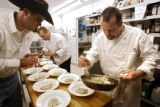 Executive Chef Bob Isaacson (cq, far right) plates a Black Truffle and Fava Bean Risotto with...