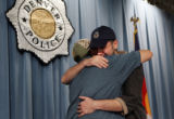 Keegan Price, cq, 12, hugs his father Lance Price, cq, as after a press conference during which...