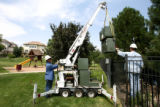 Xcel Energy lineman Brenda Lott, cq, carefully lowers a new transformer Monday July 17, 2006 to...