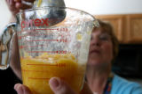 Janet Benavente(cq) measures out a quantity of peach preserves to make peach jam at the Adams...