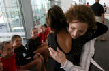 Two-time Olympian Shannon Miller, right, hugs and meets  members of 5280 Gymnastics Tuesday...