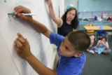 Fifth-grader Shawn Glover writes an exclamation mark on the board during a punctuation exercise in...