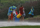 Visitors to Hyland Hills Water World, 1800 W. 89th Ave., head for their cars in the heavy rain...