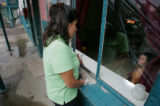 Jessica Perez, CQ, left, a migrant outreach coordinator speaks in Spanish with a woman through an...