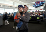 Tom Hawat carries his five-year-old son Elijah through Denver International Airport moments after...