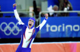 Italian skater Enrico Fabris raises his arms in victory after finishing third with a time of...