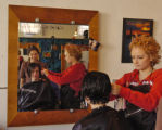 Nathalie Lien (cq), middle, gets her hair cut by stylist Talie Ayers (cq) , right, while Erynn...